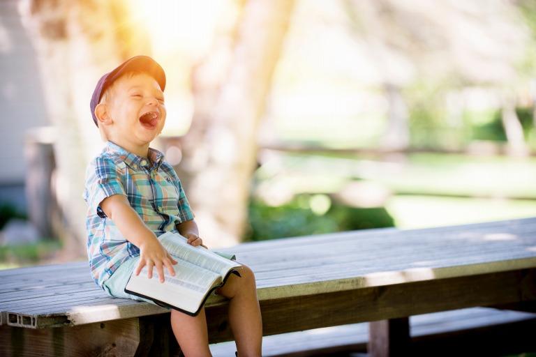 男の子が本を読んで笑っている