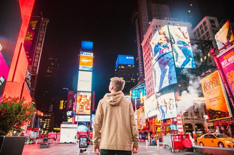 男性が街にある数々の広告を見ている